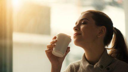 persoon die drinkt uit een bedrukte koffiebeker als promotiemateriaal